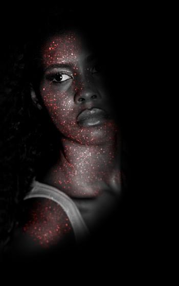 attractive Black woman partially hidden in shadow